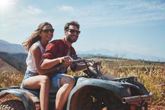 Happy young couple driving a quad bike Stock Photos