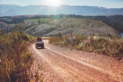 Young couple riding quad bike on country road Stock Photos