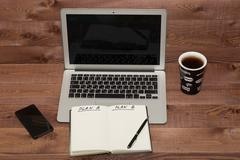 Notebook with business plan, phone, laptop. coffee cup on table - stock photo