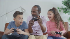 4K Happy grandfather trying to learn to play video games with grandchildren - stock footage