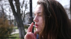 Closeup pretty young girl smoking cigarette breathing out in slow motion smoke Stock Footage