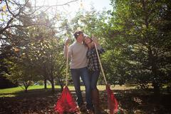 Affectionate couple with leaf rakes - stock photo