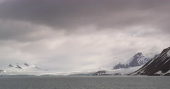 Rocky snowy mountains across an arctic bay Stock Footage