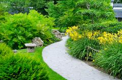 summer park with paths and flower beds - stock photo