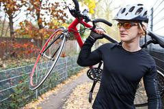 Cyclist carrying bike Stock Photos