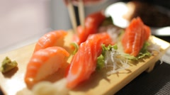 Plate of sashimi sushi raw salmon, chopsticks takes one piece Stock Footage