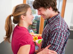 Smiling couple hugging in kitchen - stock photo
