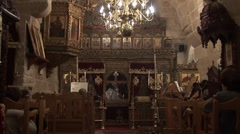 Cypriot Greek Orthodox church service, zoom out from priest to nave Stock Footage