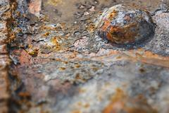 Detail shot of a rusty steel beam with a rivet. - stock photo