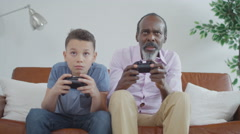 4K Happy grandfather trying to learn to play video games with grandson at home.  - stock footage