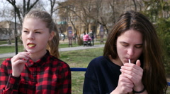 Young girls on a bench smoke cigarette and eating potato chips crisps Stock Footage