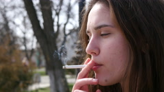 Young girl from high school face closeup smoking cigarette in public place Stock Footage
