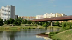 View of the prefabricated buildings in the distance - pond in the park - bridge Stock Footage