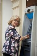 Mature blonde woman counting money near ATM Stock Photos