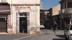 Greek Cypriot old town street scene, kids bike past barber Stock Footage
