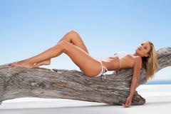 Woman in bikini laying on log Stock Photos