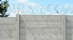 tall concrete block wall with barbed wire in the countryside - stock footage