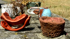 Old ceramics objects stand on the brick wall  in the countryside Stock Footage