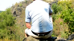 Young man sits on the cliff of the large mountain - view on his back Stock Footage