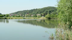 Stock Video Footage of view of the village in the distance - before pond with forest in the grassland