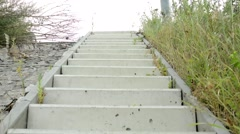 Camera focus concrete stairs - around long grass - wind blows wild Stock Footage