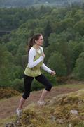Woman climbing rural hill - stock photo