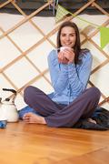 Woman drinking tea in living room - stock photo