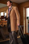 Businessman rolling luggage in lobby Stock Photos