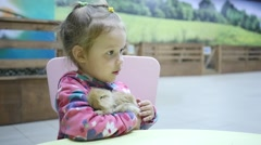 Kid and animal - Little happy girl holding a fluffy rabbit on hands slow motion Stock Footage