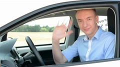 Young handsome man gets in modern car - eye contact with camera - waves and leav Stock Footage