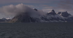 Rocky Peaks Poke through lone low cloud on sunny day Stock Footage