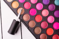Stock Photo of Eye shadow and brush for nail polish on a white wooden background