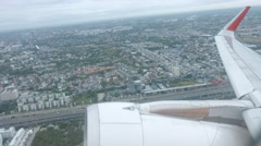 Urban center, from window of airliner, with the plane's wing and engine Stock Footage