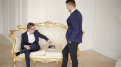 Two representative men in suits with bow ties communicate in a white room - stock footage