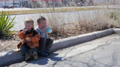 Little Boys eating Luch Sitting on a Curb. Stock Footage