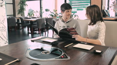 Young couple advised what to order for lunch - stock footage