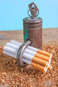 Antismoking background with broken cigarettes, tabacco and a padlock - stock photo