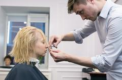 A hairdresser making haircut for a blonde female client - stock photo