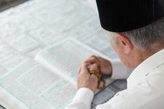 An old man reading Koran. Selective focus - stock photo