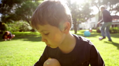 Child hanging in outdoor garden. Sunflare hits the lens giving it a backlit l Stock Footage