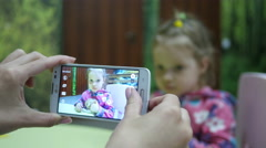 Mother fingers taking photo picture of her little daughter via smart phone Stock Footage