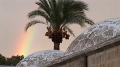 Rainbow and date palm over Turkish steam bath hamam domes Stock Footage