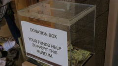 Donation Box With Money in it at a museum - stock footage