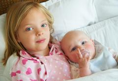 Girl hugging infant sibling in bed - stock photo