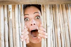 Close up of woman gasping behind fence - stock photo