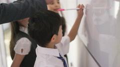 4K Happy school children in class writing on board with teacher - stock footage
