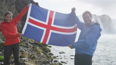 Excited Couple Holding Iceland Flag At Godafoss Iceland Tourist Destination Stock Footage
