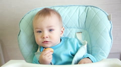 Little Boy Eats While Sitting In The Highchair Stock Footage