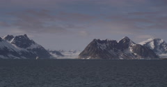 Passing Snowy Coastal Mountains in Arctic on Sunny Day Stock Footage
