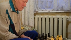 Stock Video Footage of Elderly Man Thinks About His Move in Chess Sitting About a Chessboard